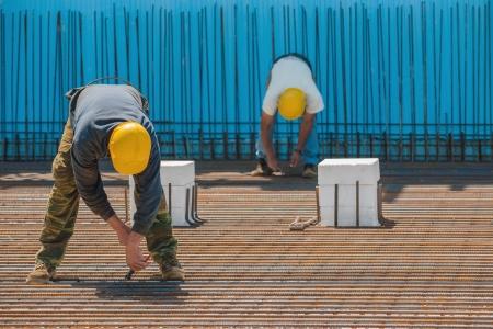 obrero: Auténticos trabajadores de la construcción la instalación de cables de unión a las barras de acero de refuerzo en frente de una superficie azul aislada antes de verter el hormigón Foto de archivo