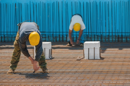 job site: Authentic construction workers installing binding wires to reinforcement steel bars in front of a blue insulated surface prior to pouring concrete