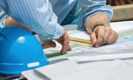 Hands of construction professionals discussing details of project over drawings Stock Photo - 15984731