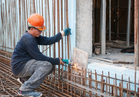 Authentic construction worker cutting steel rods with electrical saw