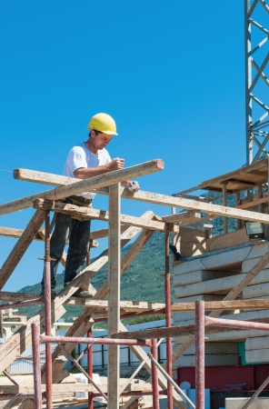 Construction worker on scaffold busy with guiding strings