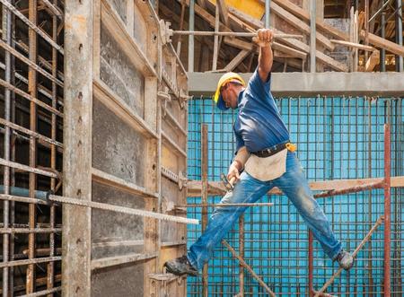 Auténtico trabajador de la construcción en una posición difícil equilibrio entre andamios y encofrados marco