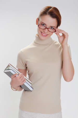 beautiful girl with books and wearing glasses in a beige jacket photo