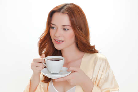 nice girl in beige home dressing gown with a cup of coffee photo