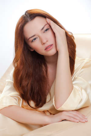nice girl in beige home dressing gown with headache photo