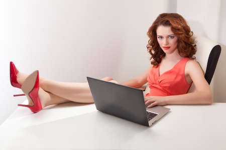 beautiful girl in  pink dress sitting in  office chair behind a white Desk with his feet on  table