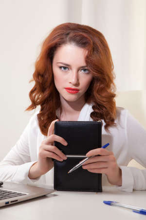 Beautiful young business woman with laptop in office