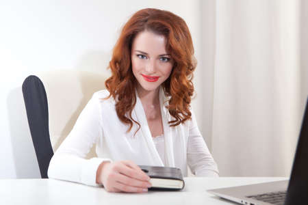 Beautiful young business woman with laptop in office photo