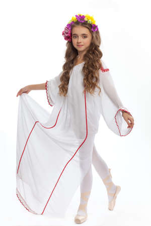 young girl in ballet shoes and long white dress with long hair  color of chestnut tree  in  the dance pose