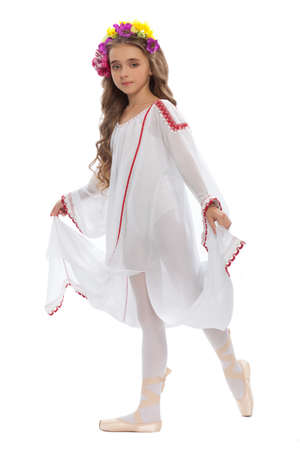 young girl in ballet shoes and long white dress with long hair  color of chestnut tree  in  the dance pose photo