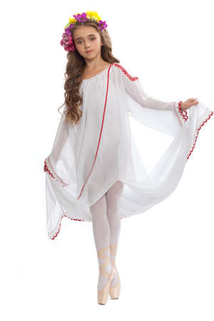 dance preteen: young girl in ballet shoes and long white dress with long hair  color of chestnut tree  in  the dance pose