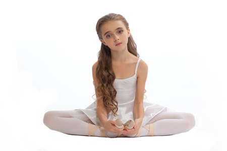long toes: beautiful teen girl in white clothes  ballet pose with long hair isolated on white background