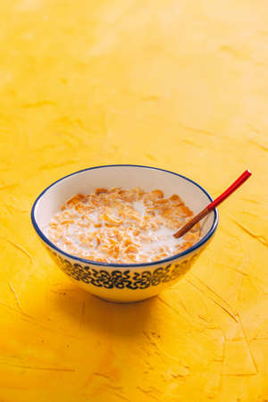 Simple Breakfast Cornflakes on Yellow Background