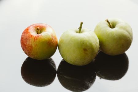 several fresh ripe apples on a dark background. Stock Photo