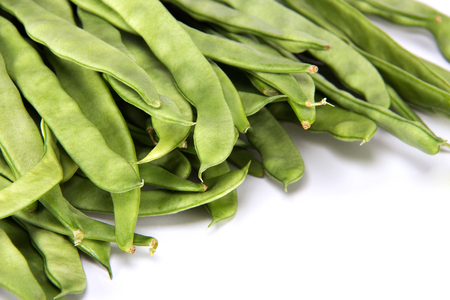 Close up of a stack of healthy and fresh uncooked string green beans isolated on white