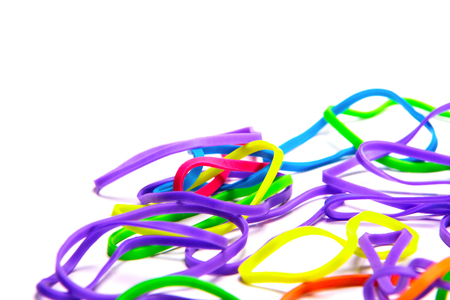 Scattered yellow, green, orange and red rubber bands on a white table. Fun and creative handmade multicolor bracelet crafts for young girls.