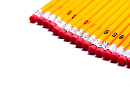 A row of yellow pencils with pink erasers isolated on white with copy space 写真素材