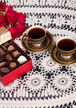 A box of fancy chocolates next to two vintage european style coffee cups on a crochet tablecloth