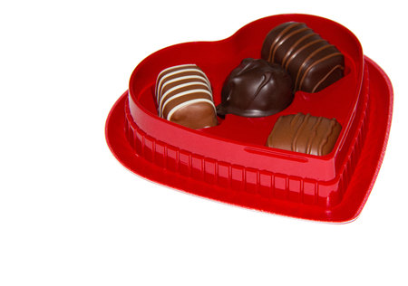Red heart shaped box of chocolates on a white background with text space