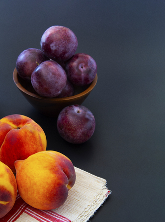 Table filled with multiple peaches and plums and a wooden bowl filled with more fruits in the background.   Healthy nutritious snacks.