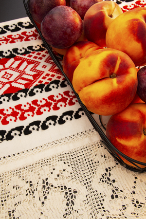 Table filled with multiple peaches and plums sitting on black wire basket on a red and black kitchen towel.  Healthy nutritious snacks. 版權商用圖片