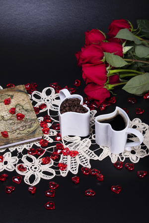 Two white heart shaped coffee cups next to red roses, a journal and scattered pink glass hearts, text space 스톡 콘텐츠