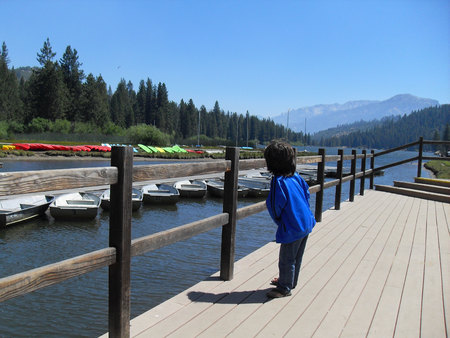 Young child watching boats in the river at Hume Lake Camp, California