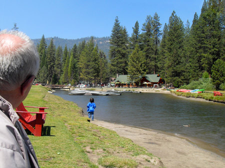 Grandfather watching child walking next to the river at Hume Lake Camp, California