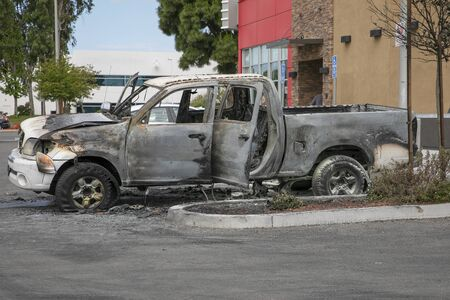 Burned car left abandoned in the parking lot. Ruined, melted, destroyed automobile.  Car insurance claim. Editorial
