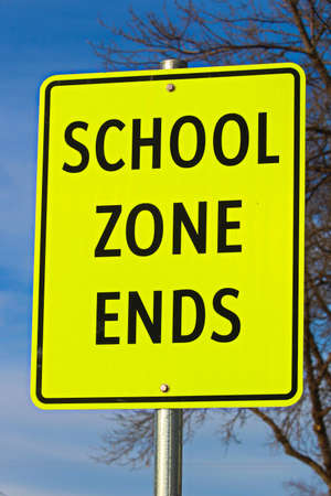 Close Up of School Zone Ends Sign Against Sky Background With Tree Imagens