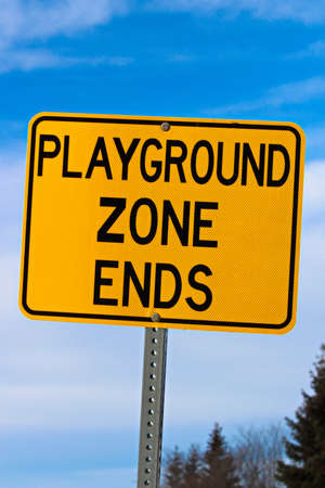 Playground Zone End Sign Against Blue Cloudy Sky and Trees