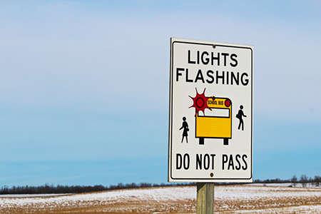 no pase: Lights Flashing School Bus Sign Along a Rural Highway Foto de archivo