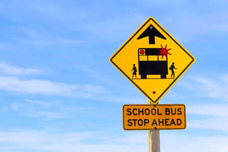 Closeup of a School Bus Stop Ahead Sign Against a Blue Sky