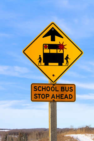 Closeup of a School Bus Stop Ahead Sign Against a Blue Sky