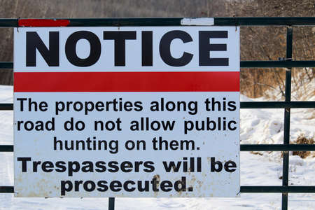 prohibido el paso: No Trespassing or Hunting Sign on a Gate