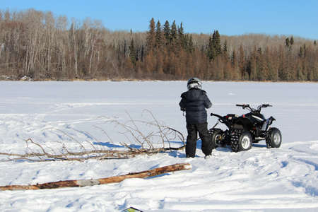 frozen lake: Pulling Firewood With a Quad to Make a Fire on the Ice Stock Photo