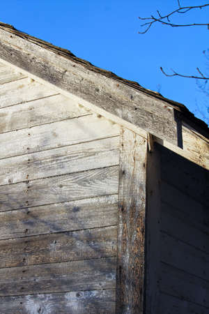 Edge of an Abandoned Farm Shed Against a Blue Sky.