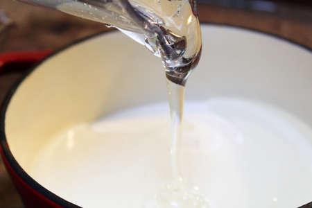 Giet heldere dikke vloeistof in een pot.
