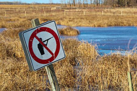 Bullet ridden sign along a wildlife pathway.