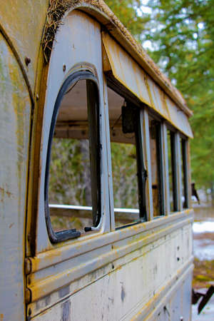 Stripped abandoned bus at a hunters camp on crown land. Stock Photo