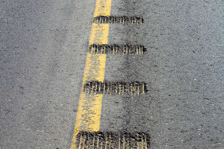 Closeup view of rumble strips on a road. Stock Photo