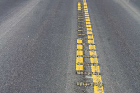 Closeup view of center rumble strips on a highway.