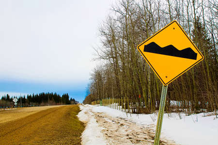 reduce risk: Warning rough road ahead sign. Stock Photo