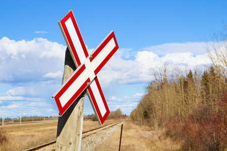 Railroad crossing sign along gravel road. Stock Photo