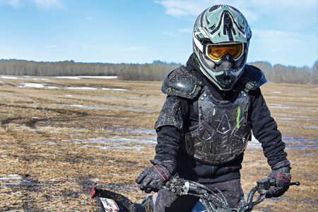 Closeup of a muddy boy in bike protection gear. Stock Photo