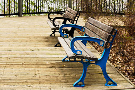 Two colorful benches on a boardwalk.