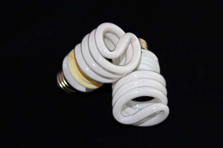 burned out: Closeup of two fluorescent light bulbs isolated on a black background.