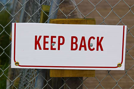 A keep back sign that has been cut in half.