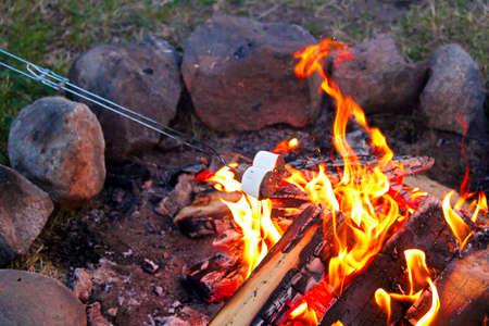 Roosteren marshmallows voor smores over een kleurrijk kampvuur.