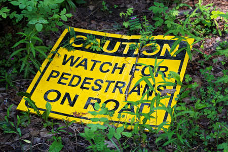 A caution watch for pedestrians on the road sign laying on the ground.